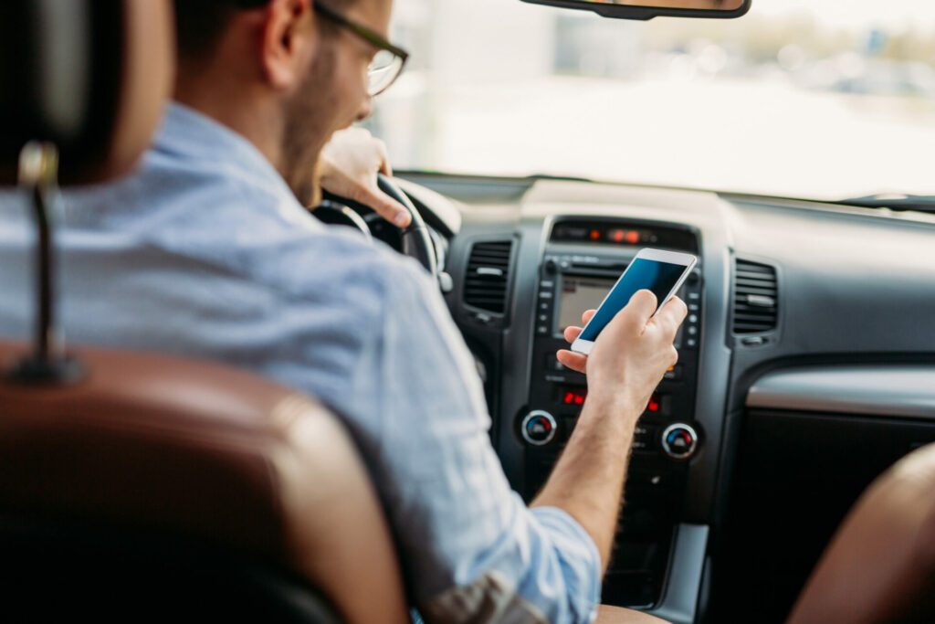 Mann som ser på telefonen mens han kjører bil.